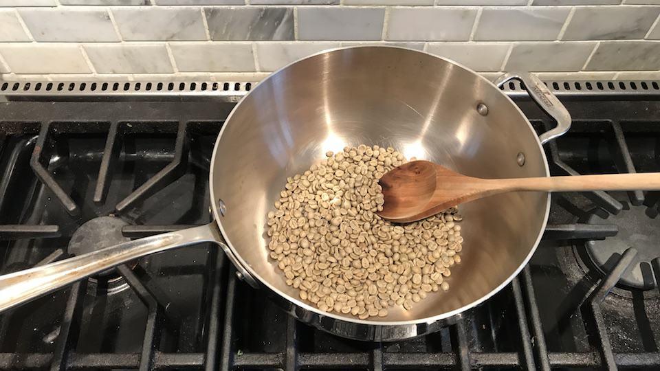 Coffee roasting in a wok on the stove