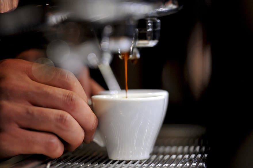 Hands pulling espresso shot