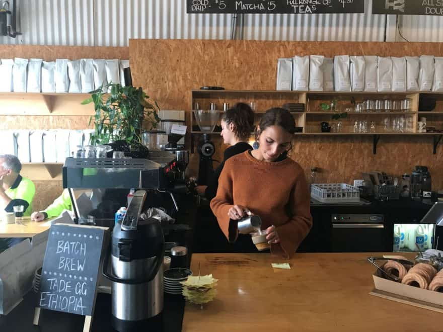 Barista pouring milk at Tell Henry