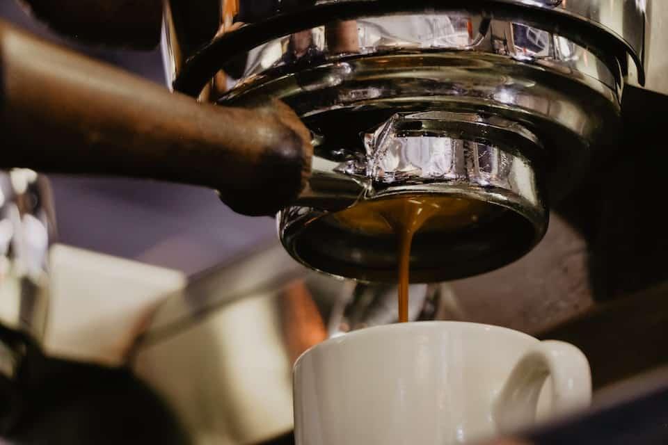 Naked portafilter extracting espresso.