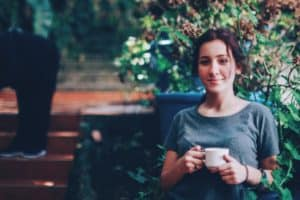 Young woman drinking coffee with a smile on her face