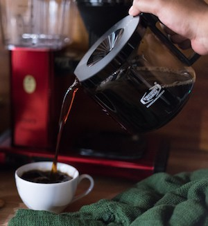 A hand pours coffee from a glass carafe into a small cup