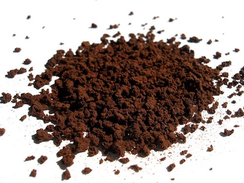 Instant coffee crystals on a plain white surface