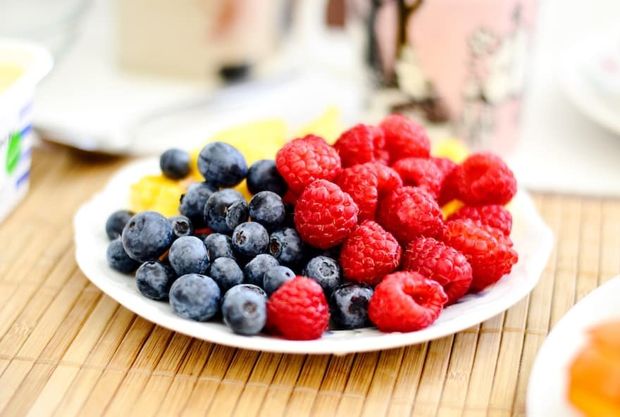 Plate of blueberries and raspberries on a picnic table