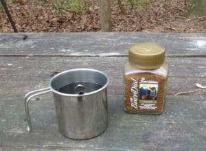 Instant coffee on a picnic table at a campsite