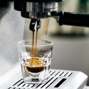 Espresso pouring from a portafilter into a glass cup