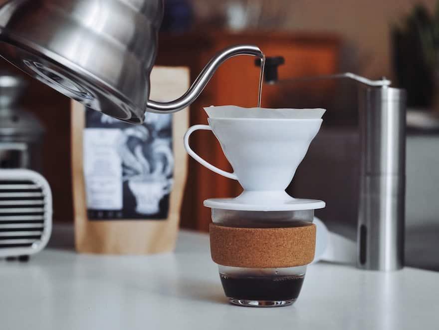 Hario gooeseneck kettle pouring into a ceramic Hario V60 coffee brewer