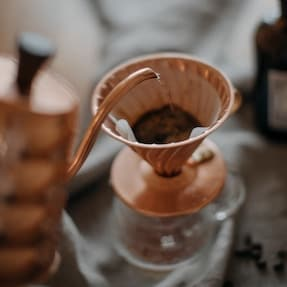 Copper kettle pouring into a copper Hario V60 coffee drip cone