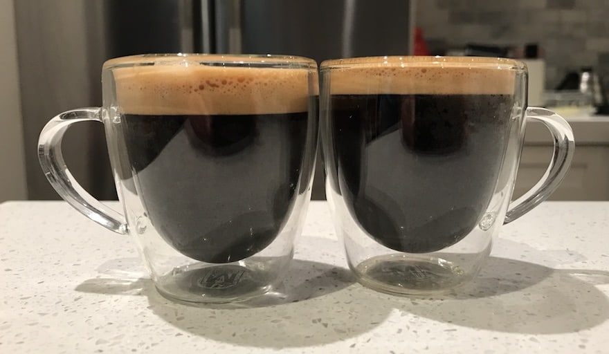 Two double shots of espresso, side by side on a counter