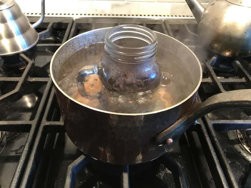 Mason jar full of coffee beans simmering in a pot of water