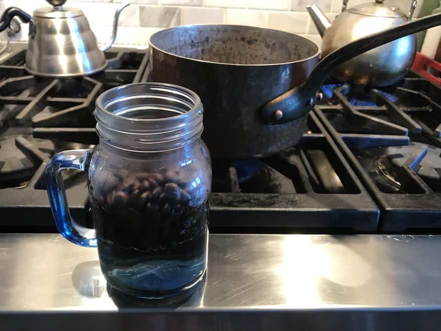 Coffee beans in a mason jar with hot water added
