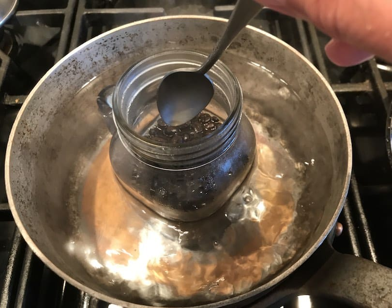 Stirring coffee beans in mason jar