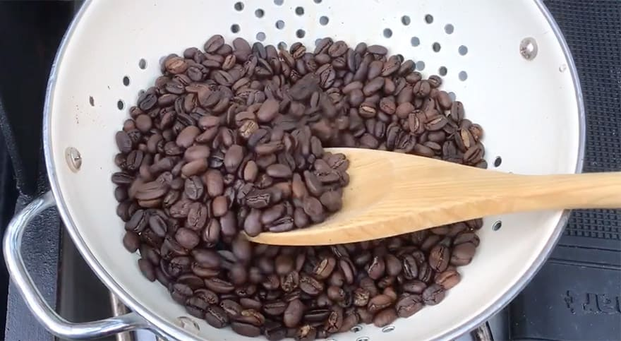 Stirring freshly roasted coffee beans in a colander with a wooden spoon