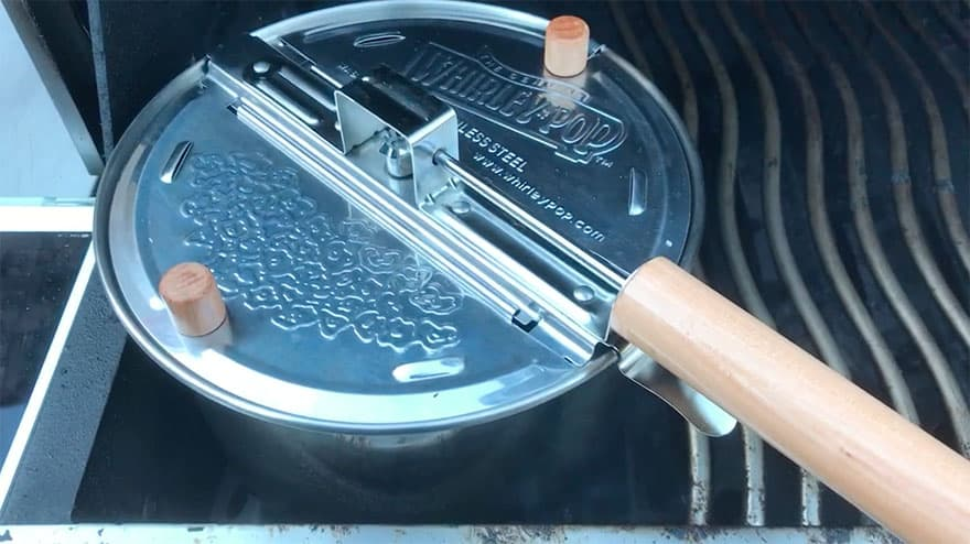 Whirley Pop popcorn popper nestled between the grates of a barbecue grill