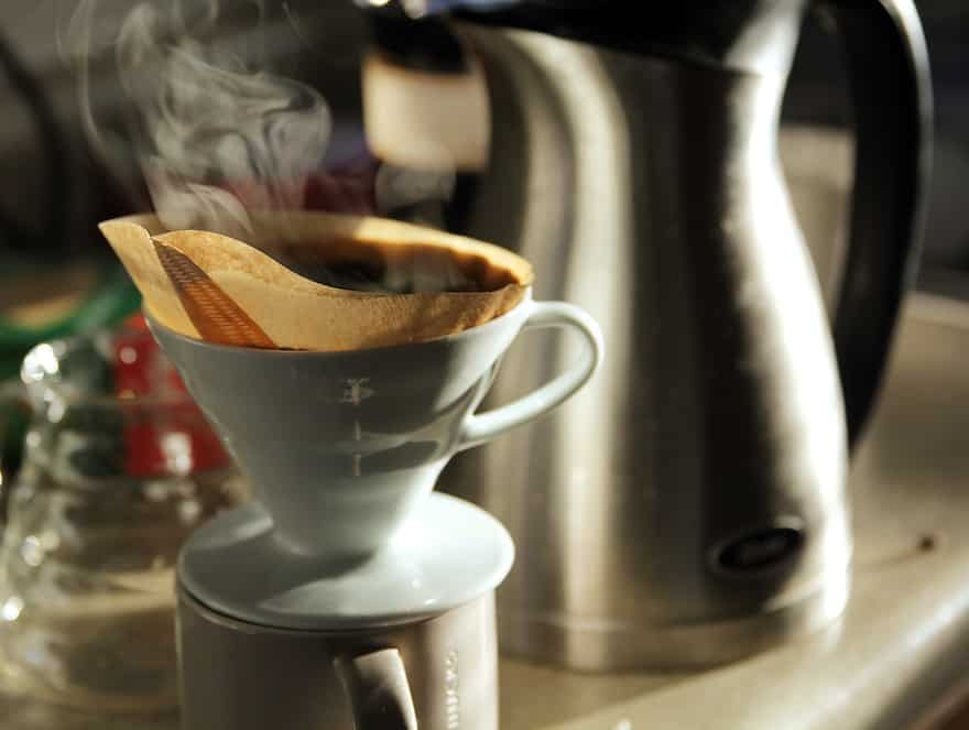 Pour over coffee drips from a Hario V60 into a mug