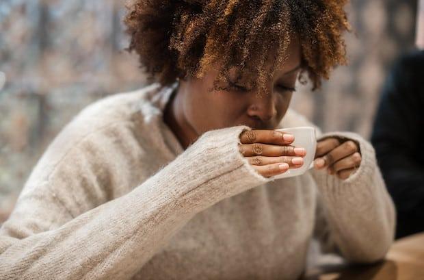 A woman tastes her coffee
