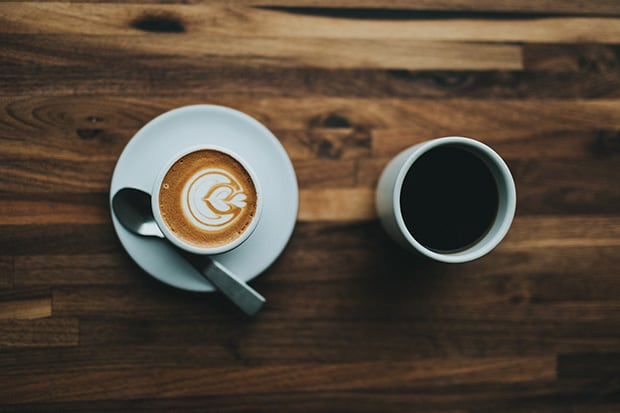 Cappuccino next to a brewed coffee on a table