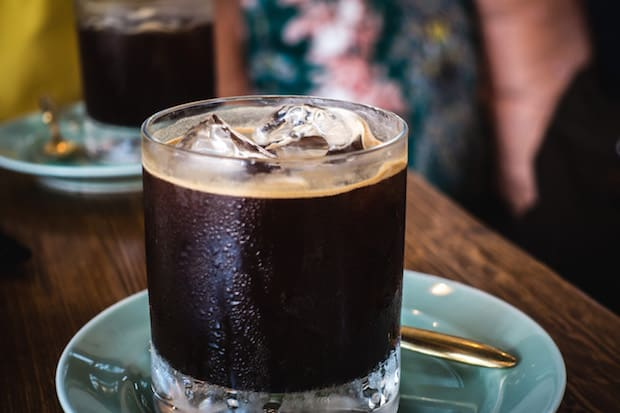 Glass tumbler full of coffee and ice