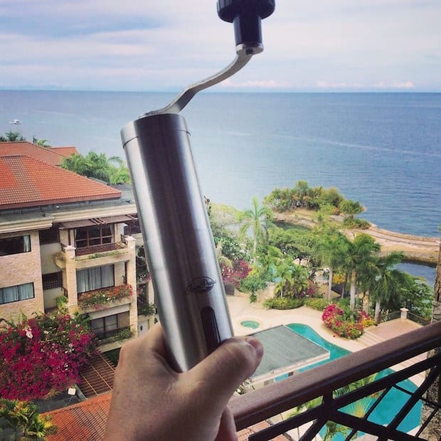 Man holding a JavaPresse manual coffee grinder on a balcony overlooking palm trees and the ocean