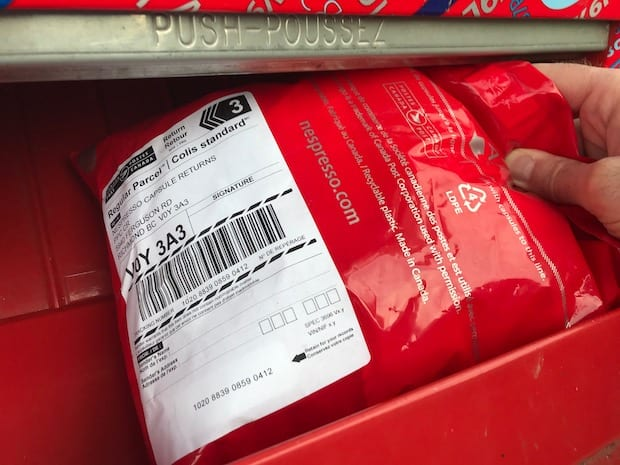 Red Nespresso recycling bag being dropped in a Canada Post mailbox.