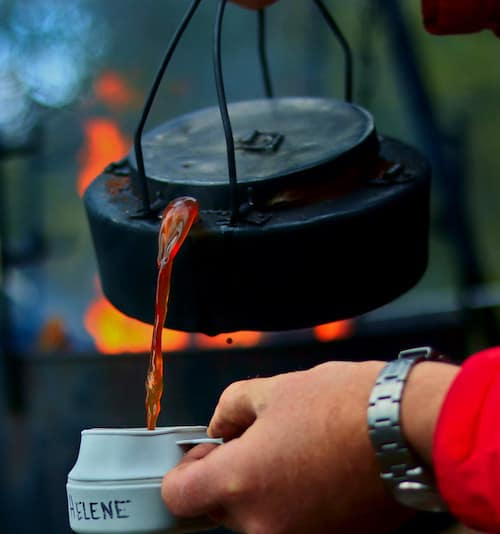 A person pours coffee from a beat-up kettle that has just come off an open fire