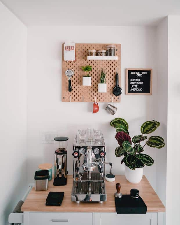 Coffee station with a pegboard on the wall above it