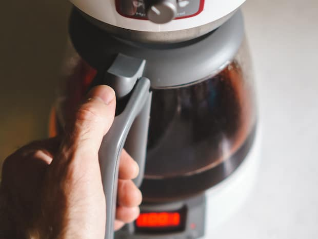 Man's hand lifting a coffee pot from a coffee maker