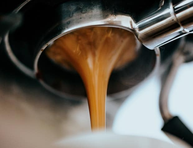 Thick stream of espresso flowing from the bottom of a portafilter