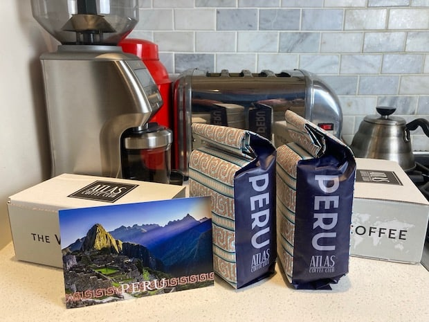 Two bags of coffee from Peru on a kitch counter next to a postcard