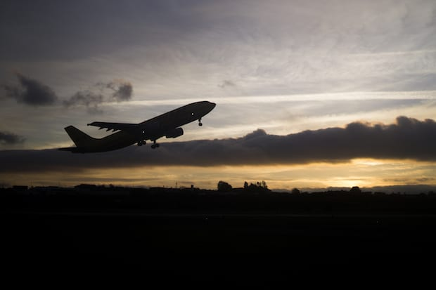 Silhouette of an airplane taking off at dusk