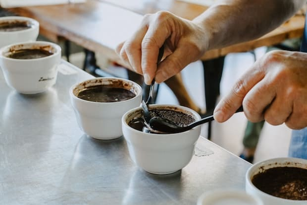 A pair of hands prepares coffee for cupping