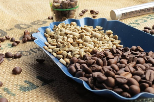A serving tray half full of raw coffee beans and half full of roasted beans