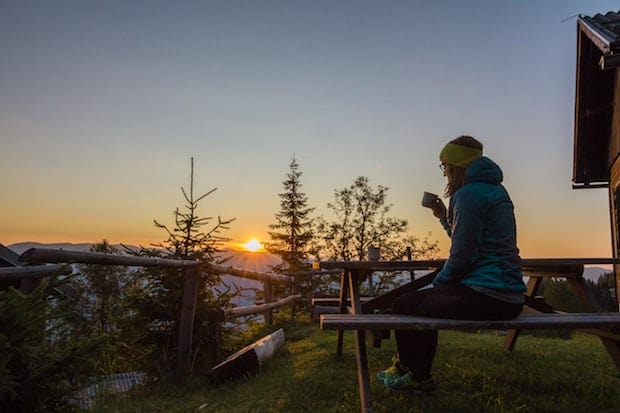woman drinking coffee on a picnic table outside a cabin in the mountains at sunrise