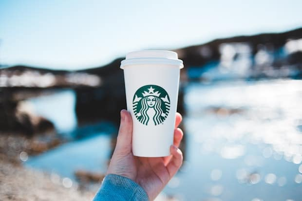 Hand holding up a Grande Starbucks cup with water and a bridge in the background